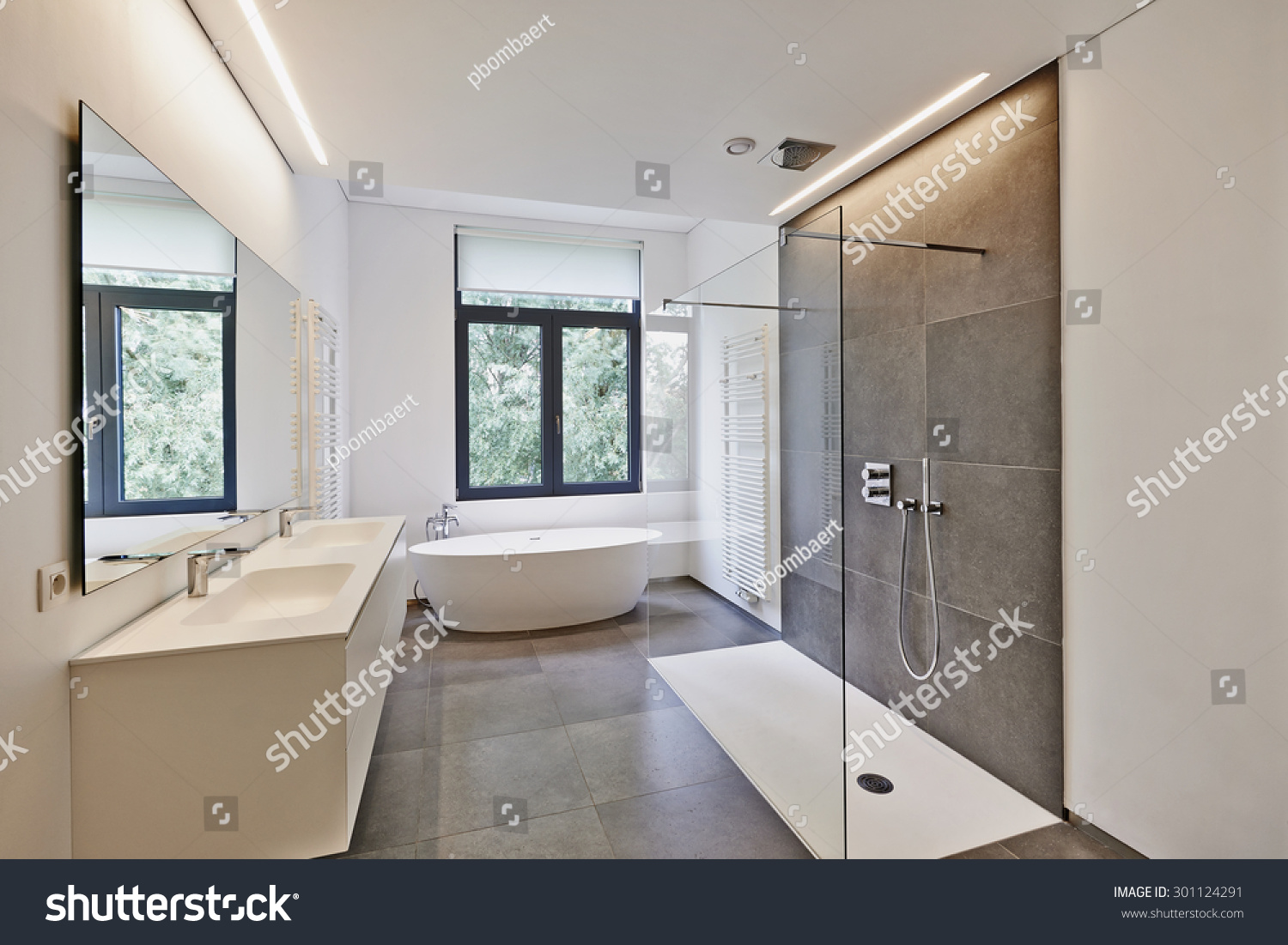 stock-photo-bathtub-in-corian-faucet-and-shower-in-tiled-bathroom-with-windows-towards-garden-301124291