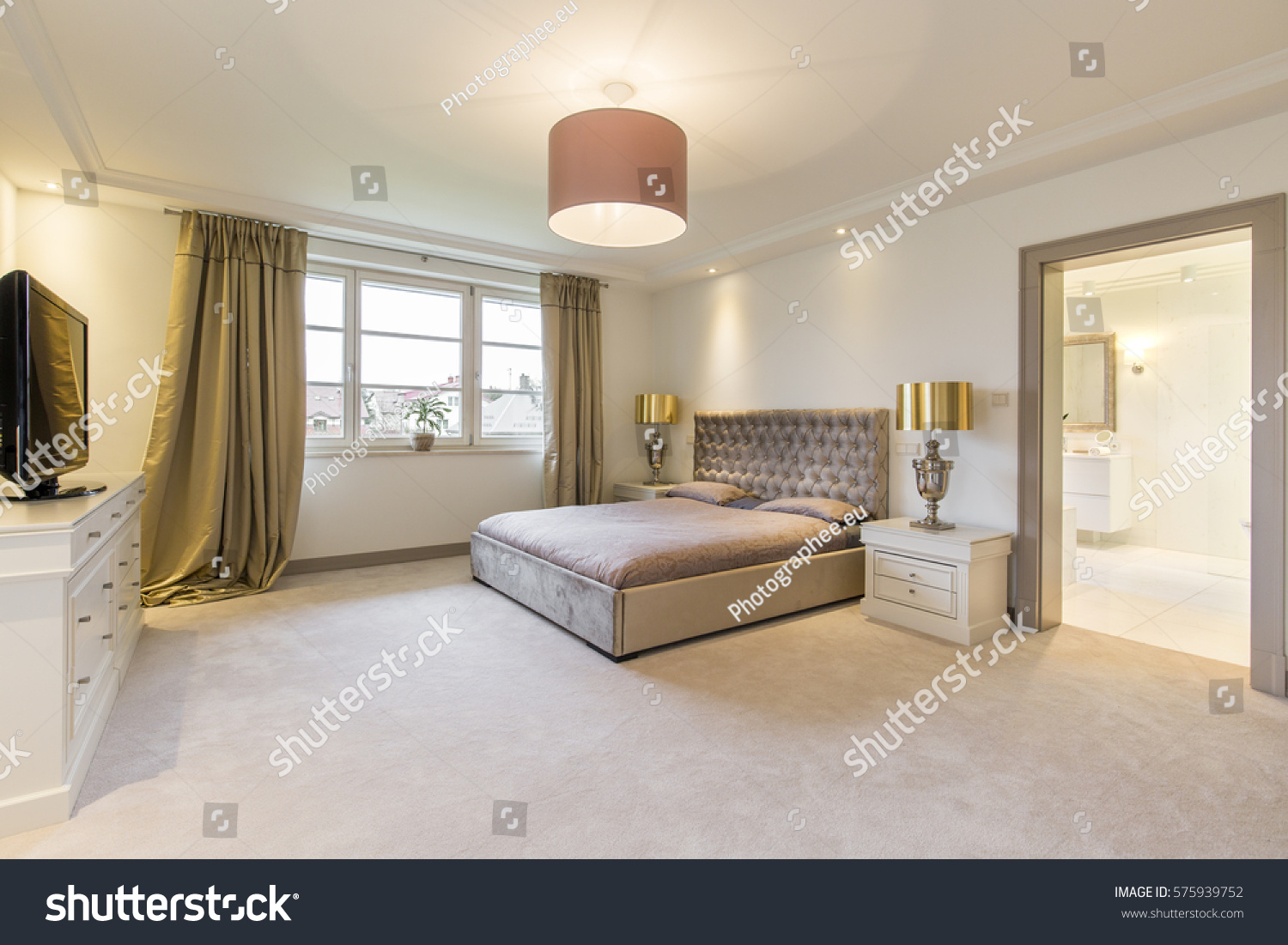 stock-photo-beige-minimalistic-bedroom-with-a-large-bed-and-golden-amenities-and-entry-to-bathroom-575939752