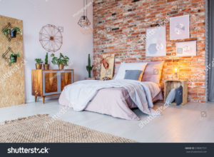 stock-photo-bright-bedroom-with-double-bed-brick-wall-and-rug-578007727