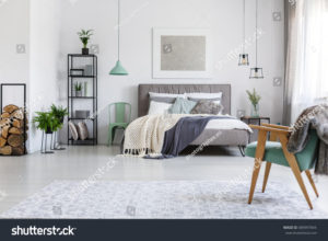 stock-photo-king-size-bed-with-blankets-and-two-mint-chairs-standing-in-stylish-hotel-room-689997844