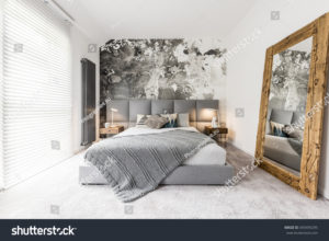 stock-photo-king-size-bed-with-gray-square-headboard-large-rustic-wooden-mirror-and-textured-wall-in-trendy-693495295