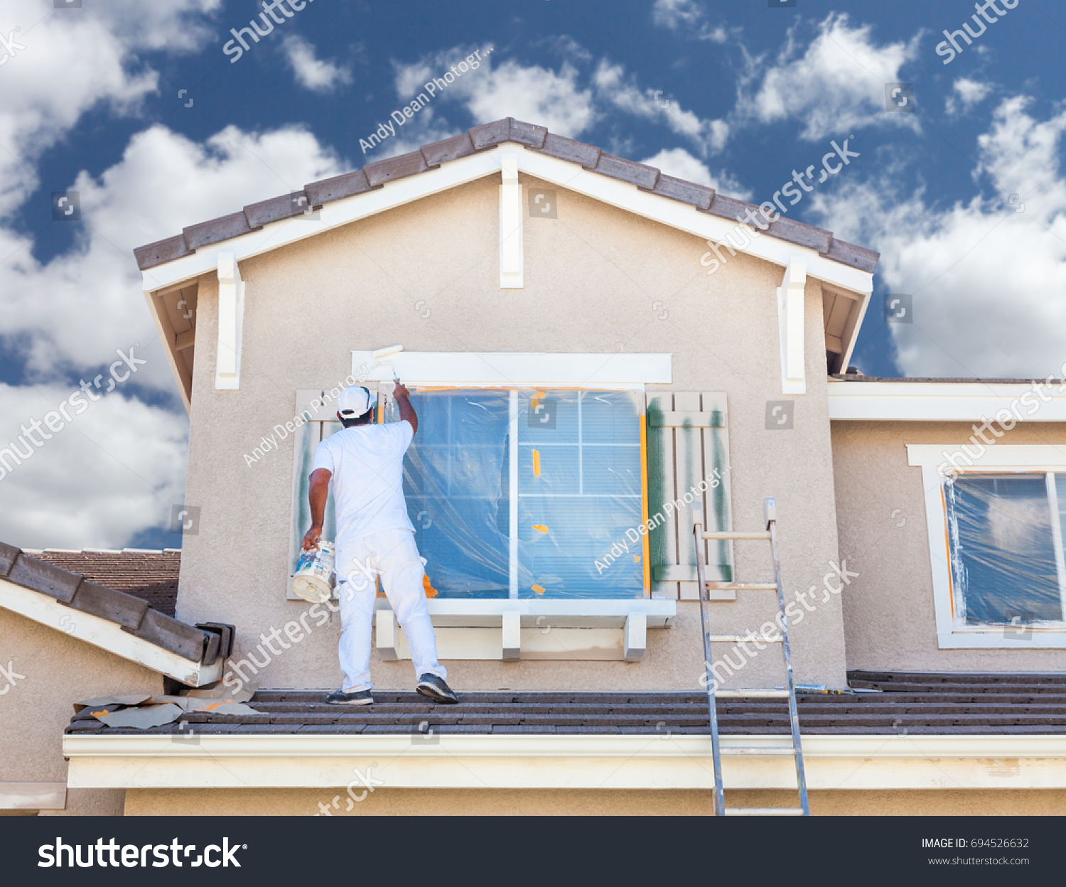 stock-photo-professional-house-painter-painting-the-trim-and-shutters-of-a-home-694526632