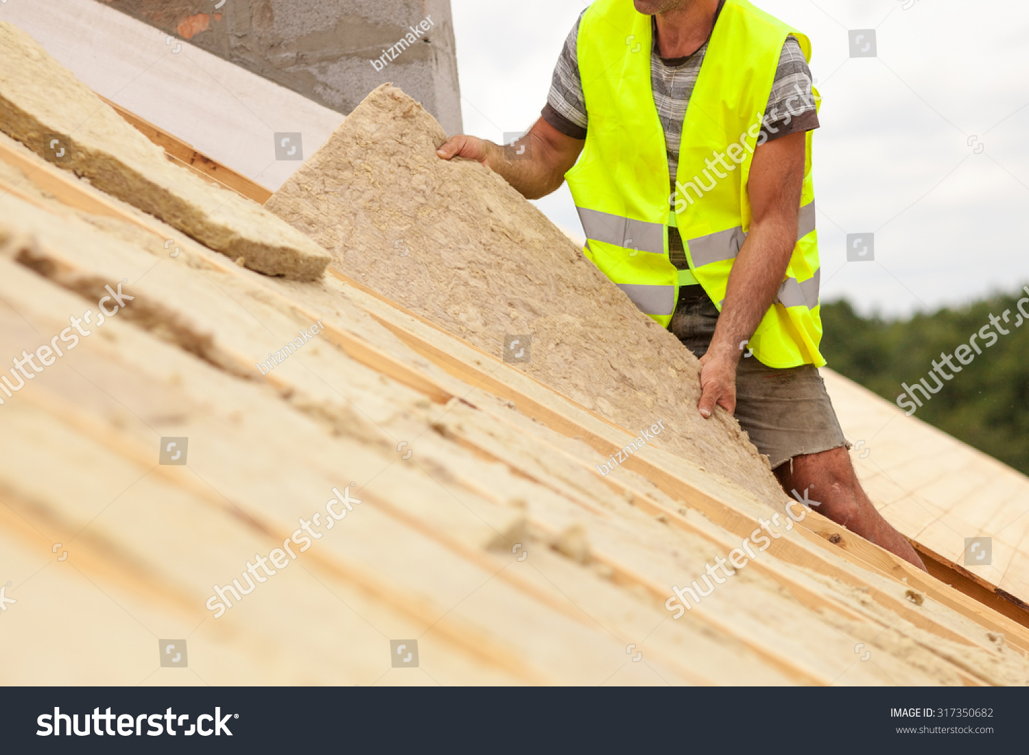 stock-photo-roofer-builder-worker-installing-roof-insulation-material-on-new-house-under-construction-317350682