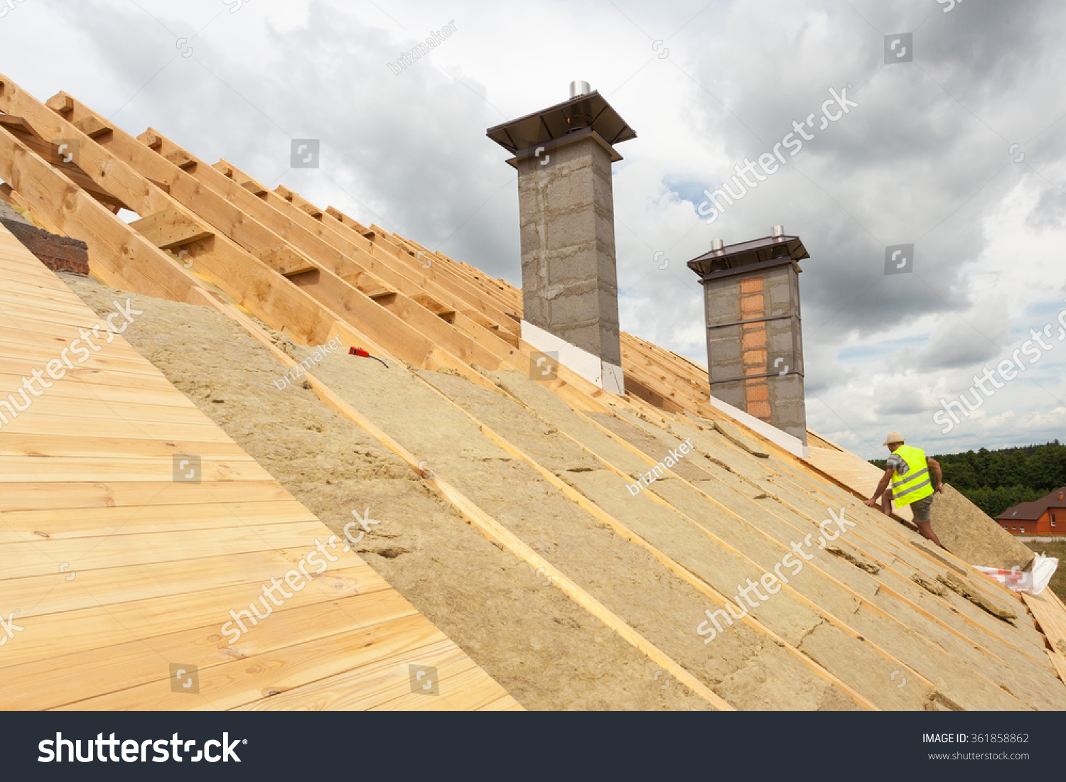 stock-photo-roofer-builder-worker-installing-roof-insulation-material-rockwool-on-new-house-under-construction-361858862
