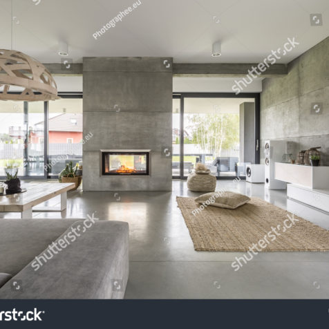 stock-photo-spacious-villa-interior-with-cement-wall-effect-fireplace-and-tv-552591889