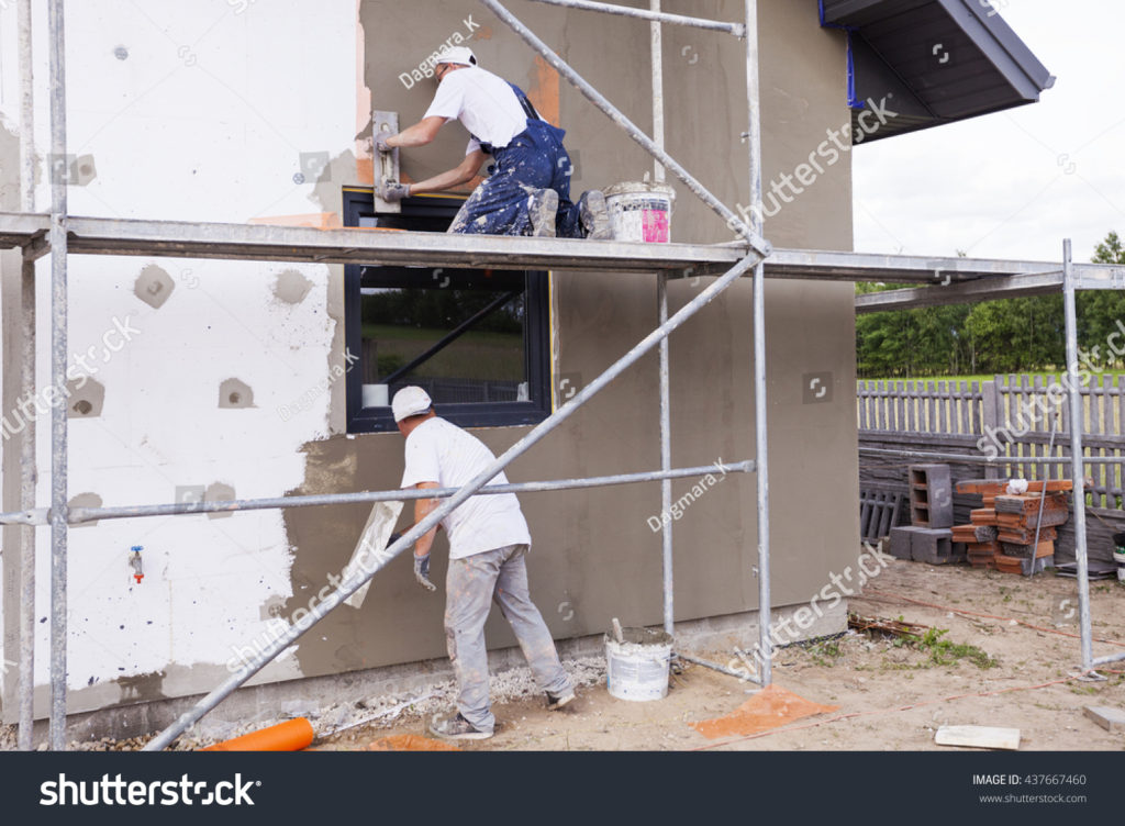 stock-photo-workers-spreading-mortar-over-styrofoam-insulation-and-mesh-with-trowel-437667460